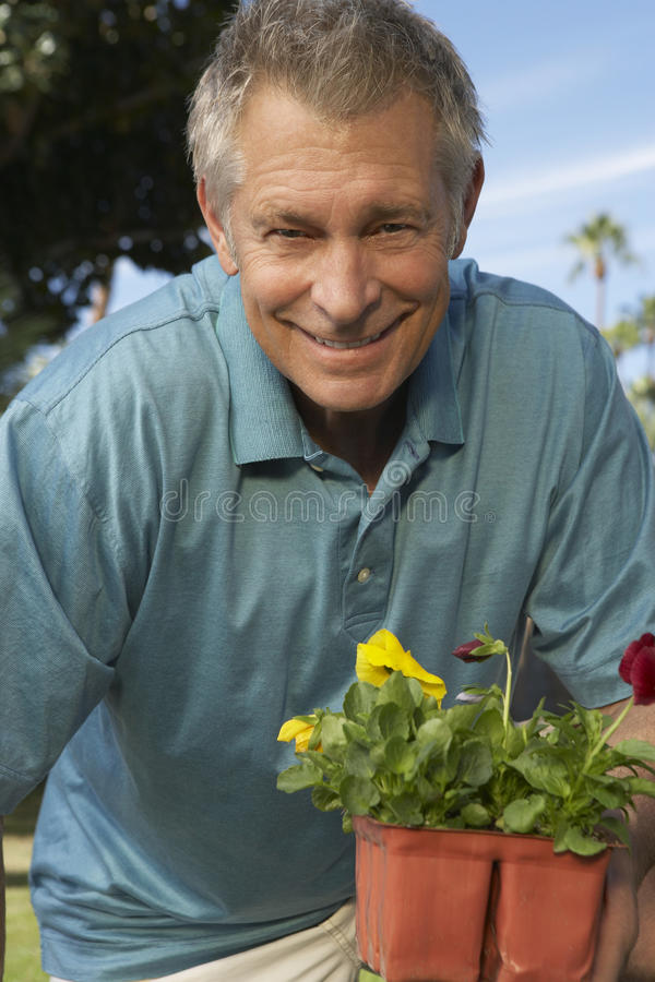 Homme supérieur avec le pot de fleur photo stock