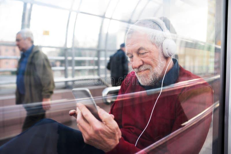 Homme supérieur avec le smartphone et les écouteurs se reposant dans le passage photo stock