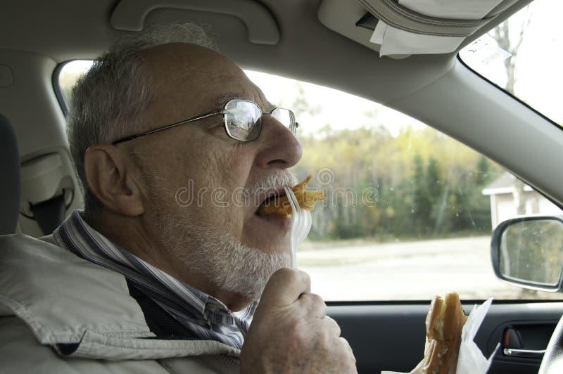 Homme supérieur avec le visage expressif mangeant des aliments de préparation rapide photos libres de droits