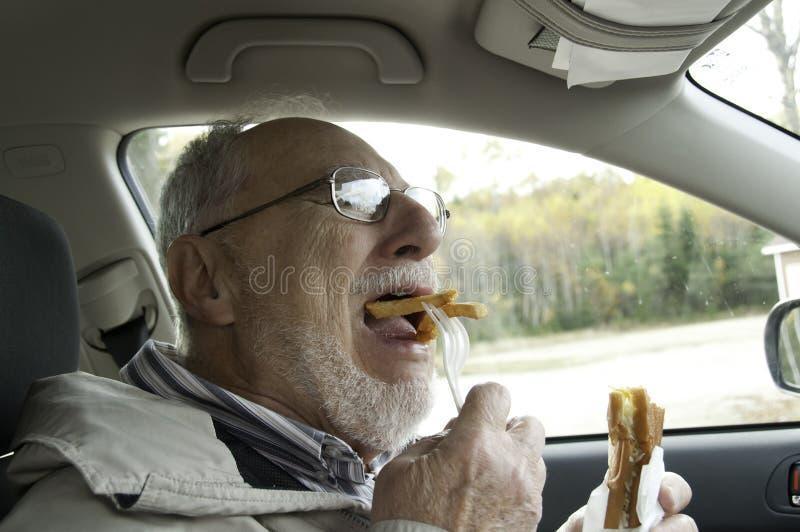 Homme supérieur avec le visage expressif mangeant des aliments de préparation rapide photographie stock libre de droits
