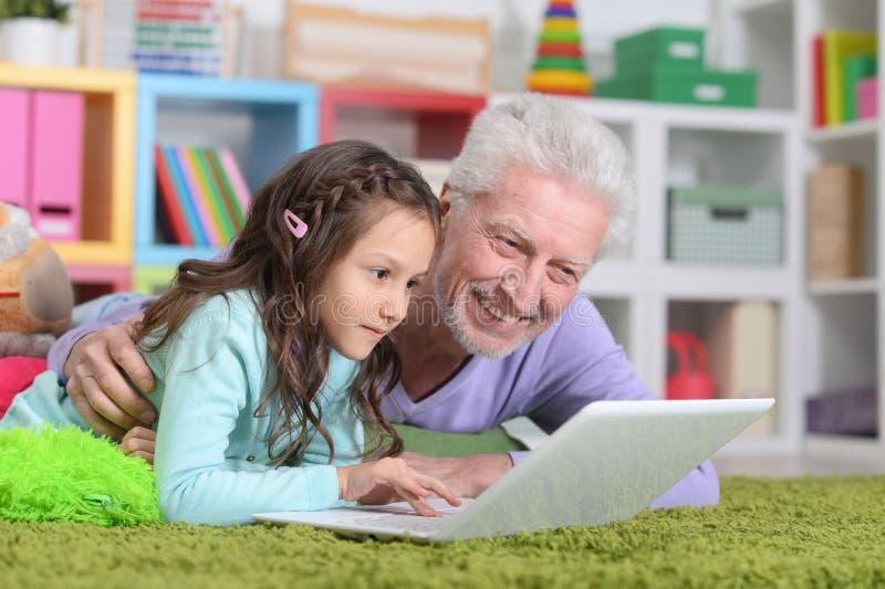 Homme supérieur avec sa petite-fille à l'aide de l'ordinateur portable photographie stock
