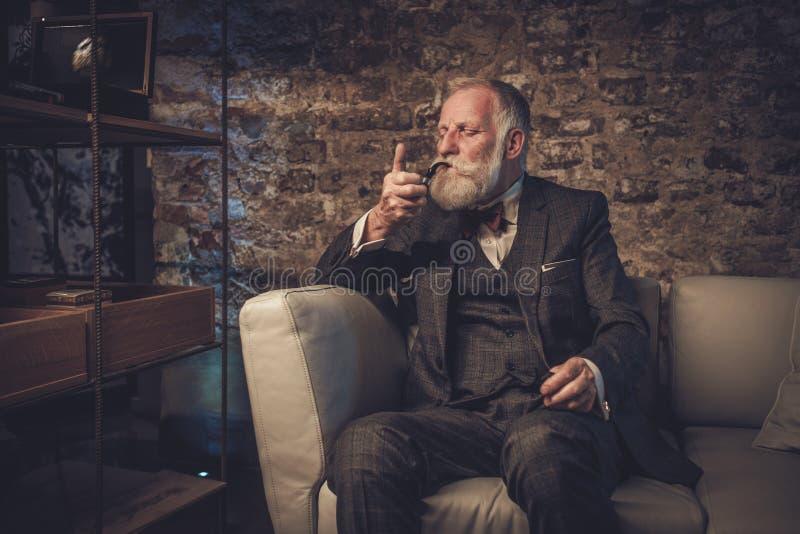 Homme supérieur avec un tuyau de tabagisme photographie stock