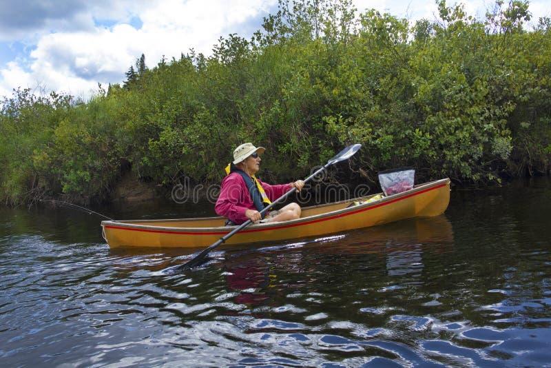 Homme supérieur barbotant un petit canoë sur la rivière d'orignaux photographie stock