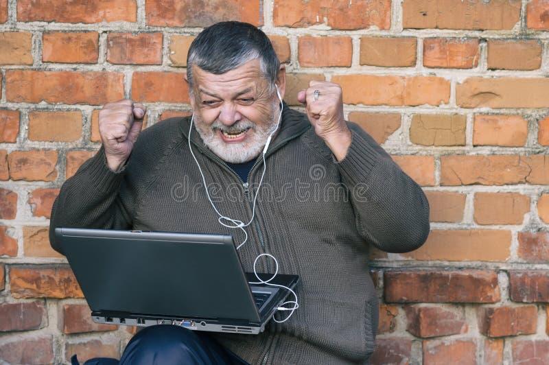 Homme supérieur barbu observant le jeu préféré sur un écran de carnet photo stock