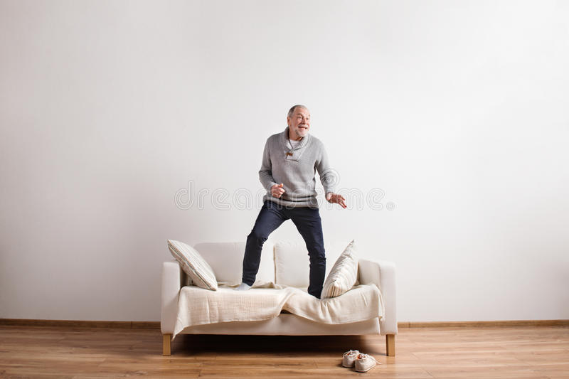 Homme supérieur bel se tenant sur le divan, dansant Projectile de studio photo stock