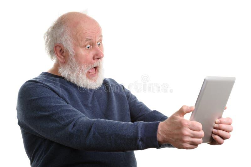 Homme supérieur choqué drôle utilisant la tablette d'isolement sur le blanc image stock