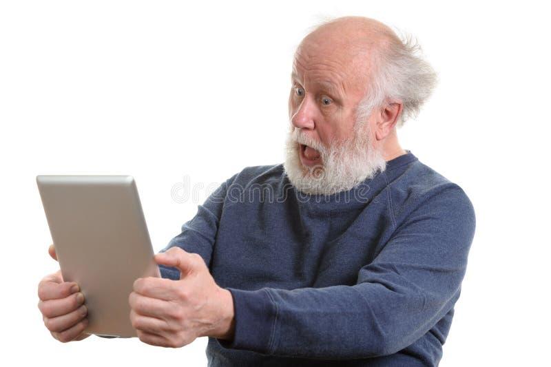 Homme supérieur choqué drôle utilisant la tablette d'isolement sur le blanc photographie stock libre de droits