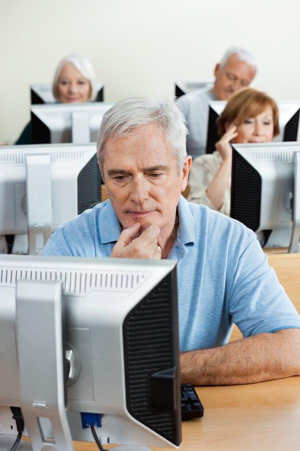 Homme supérieur concentré à l'aide de l'ordinateur dans la salle de classe image libre de droits