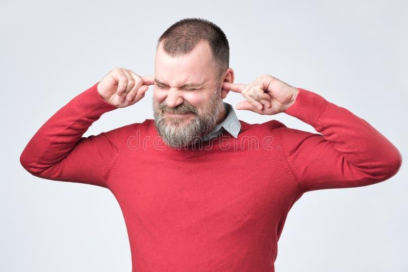 Homme supérieur, couvrant les oreilles fermées contrariées par le bruit fort ne voulant pas entendre l'histoire photo stock