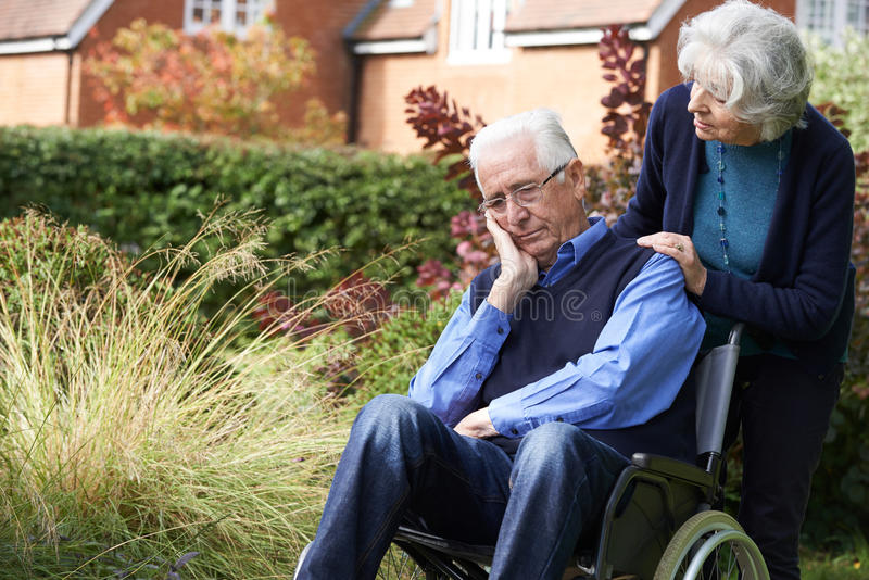 Homme supérieur déprimé dans le fauteuil roulant poussé par Wif image stock