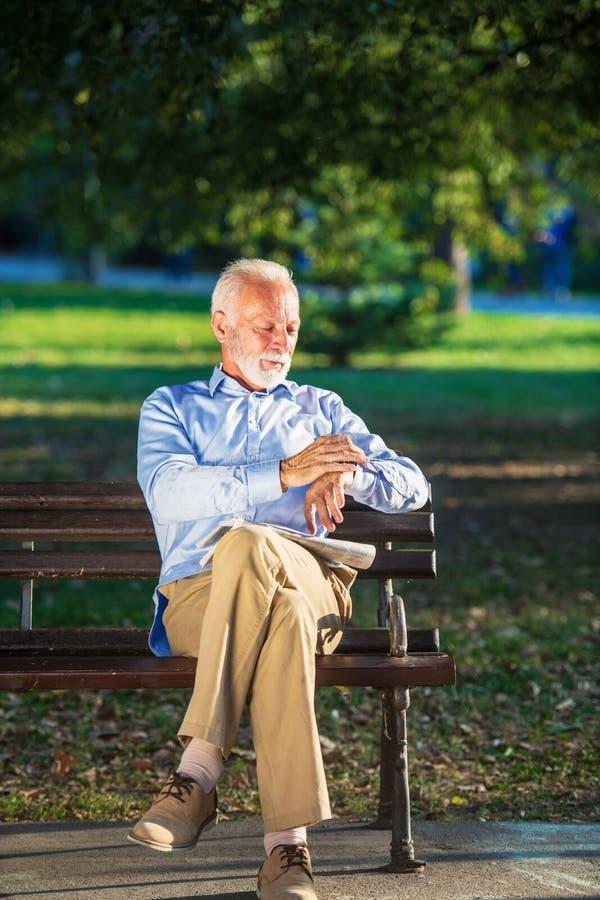 Homme supérieur détendant en parc un jour ensoleillé posé sur un banc en bois et attendant quelqu'un photographie stock libre de droits