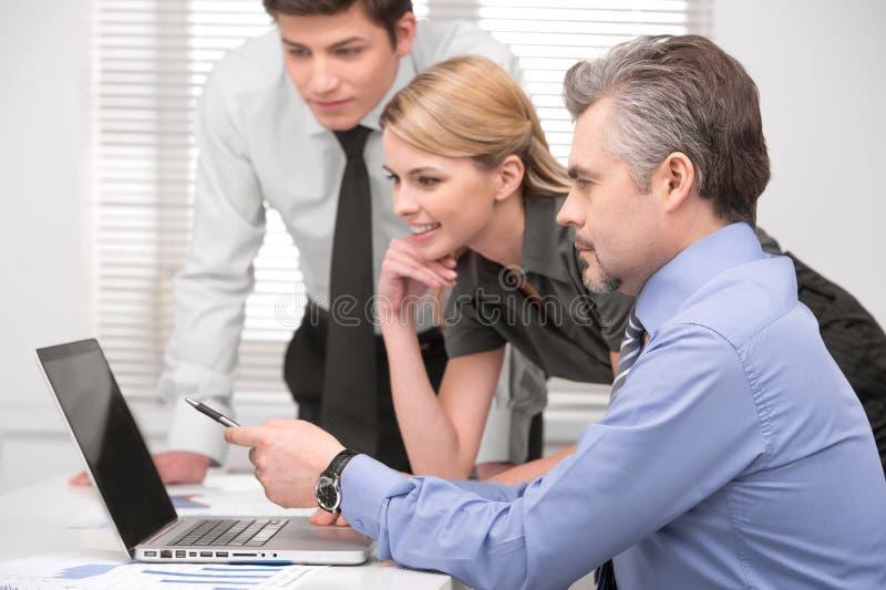 Homme supérieur d'affaires montrant quelque chose sur l'ordinateur portable. image libre de droits