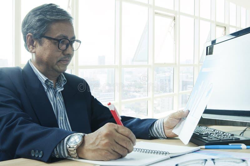Homme supérieur d'affaires travaillant à la table de bureau photographie stock
