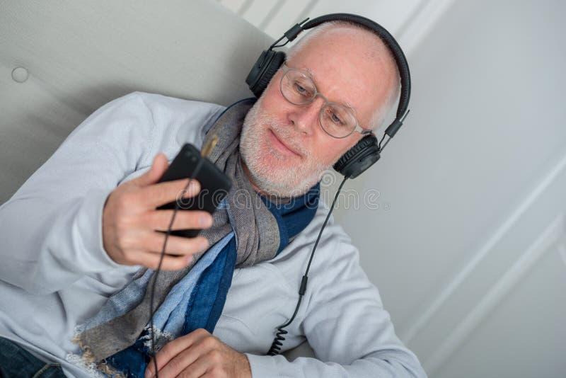 Homme supérieur dans des écouteurs écoutant la musique à la maison photographie stock