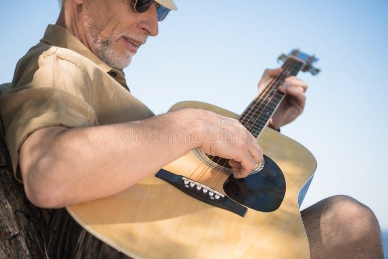Homme supérieur dans des lunettes jouant la guitare dehors photographie stock libre de droits