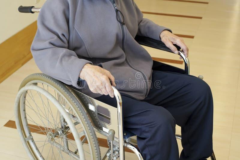 Homme supérieur dans le fauteuil roulant au couloir d'hôpital photos libres de droits