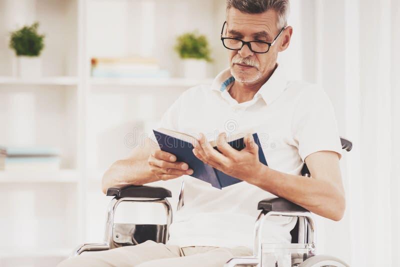 Homme supérieur dans le livre de lecture de fauteuil roulant à la maison photos stock