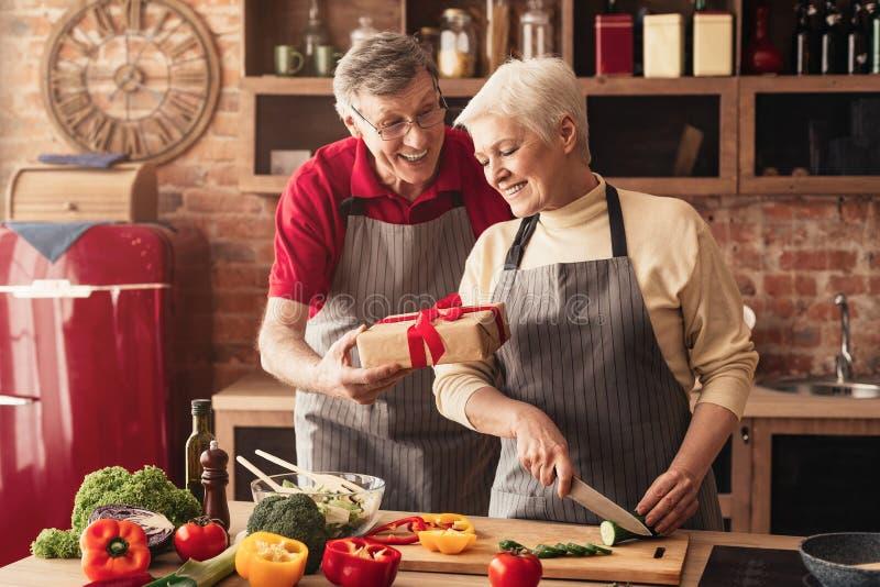 Homme supérieur de soin donnant le boîte-cadeau à son épouse à la cuisine photos stock