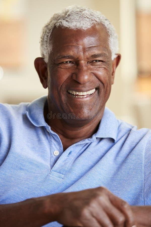 Homme supérieur de sourire détendant sur Sofa At Home photo stock