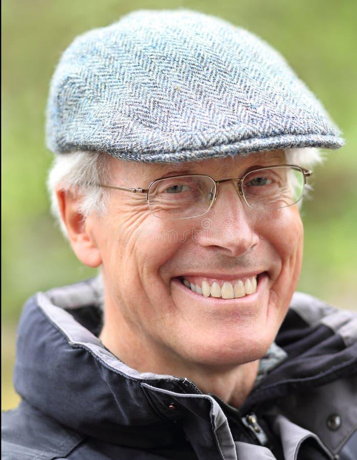 Homme supérieur de sourire dehors avec les verres et le chapeau images stock