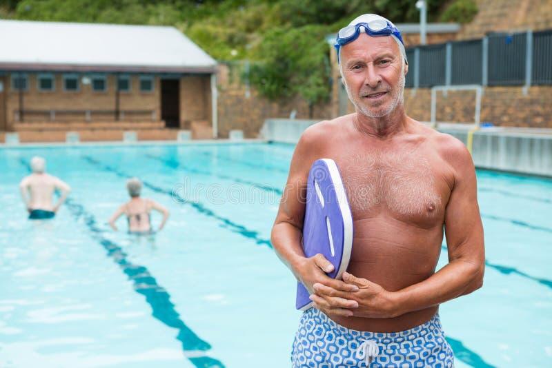 Homme supérieur de sourire tenant le kickboard au poolside image libre de droits
