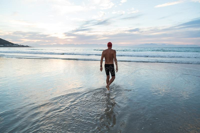 Homme supérieur disposant à nager en mer à l'aube images stock