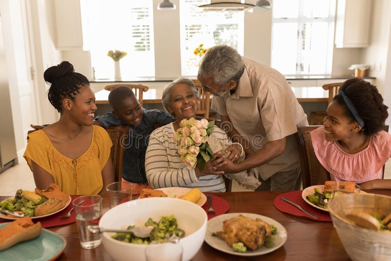 Homme supérieur donnant le bouquet de fleur à la femme supérieure tout en ayant le repas sur la table de salle à manger photos stock