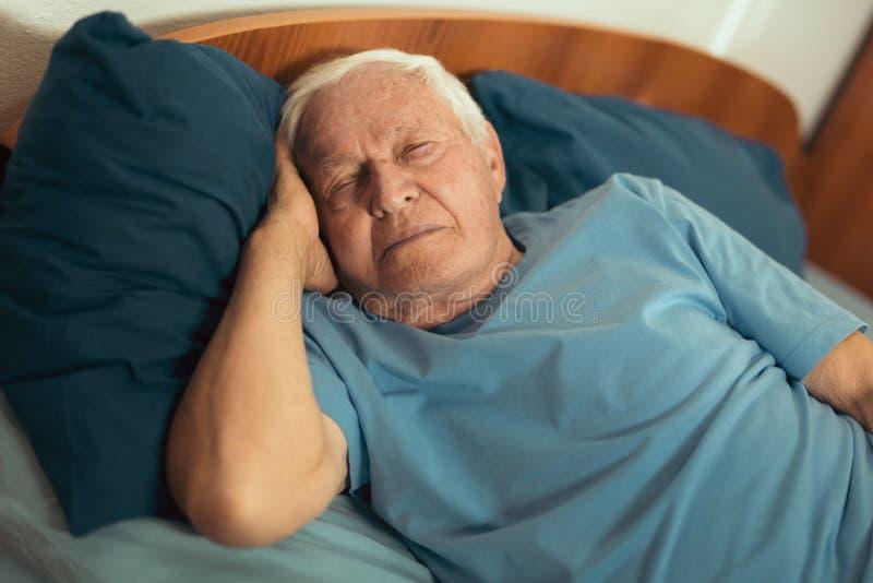 Homme supérieur dormant sur le lit photo libre de droits
