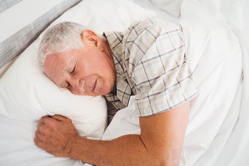 Homme supérieur dormant sur le lit image stock