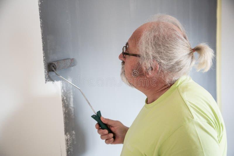 Homme supérieur drôle peignant le mur photographie stock libre de droits