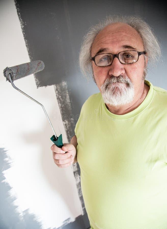 Homme supérieur drôle peignant le mur image libre de droits