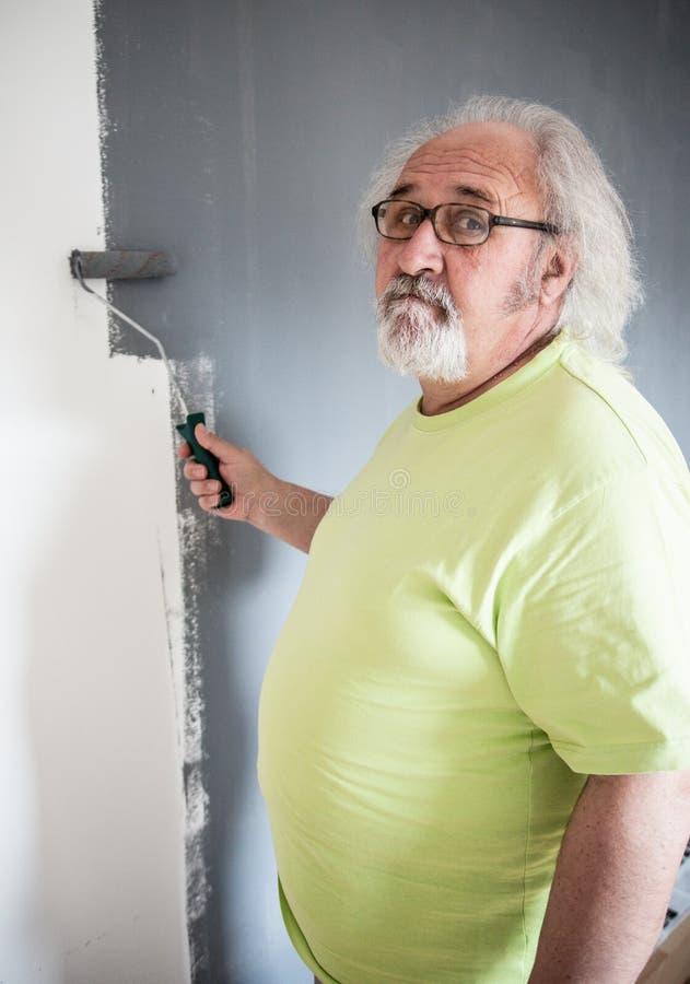 Homme supérieur drôle peignant le mur photo libre de droits