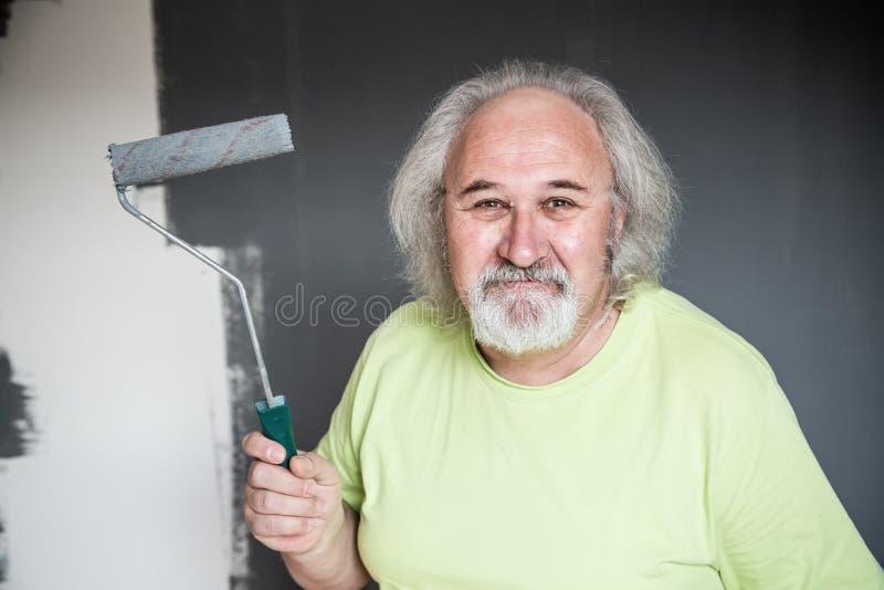 Homme supérieur drôle peignant le mur photos libres de droits