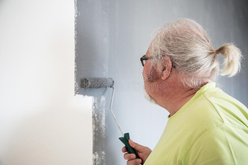 Homme supérieur drôle peignant le mur photographie stock