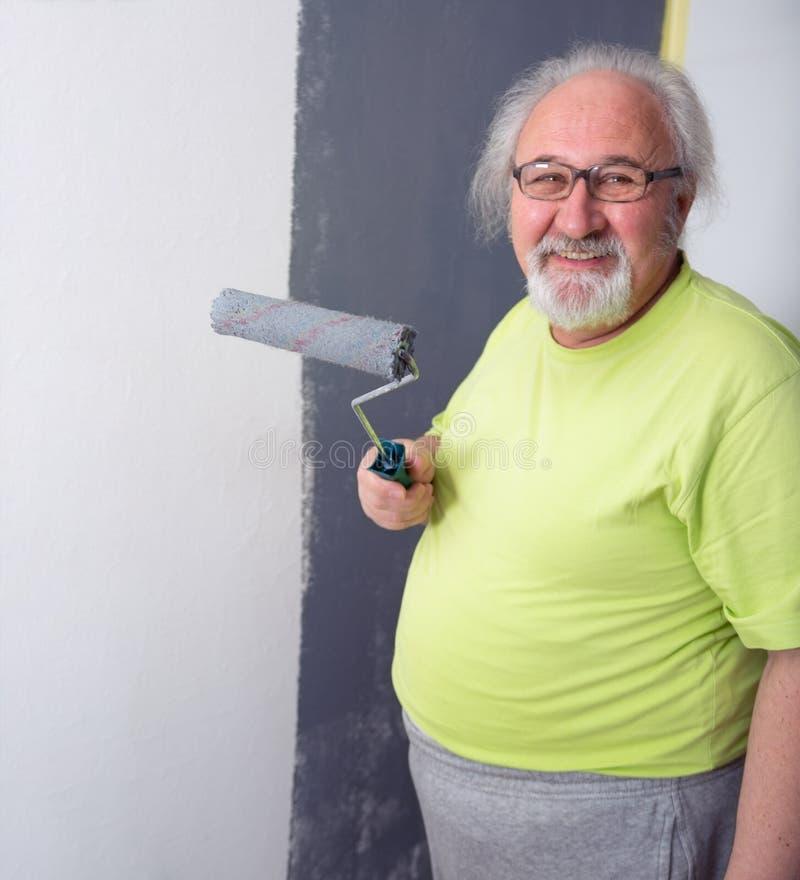 Homme supérieur drôle peignant le mur images stock