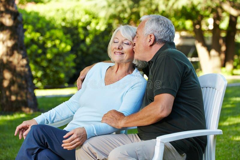 Homme supérieur embrassant la femme dans le jardin images stock