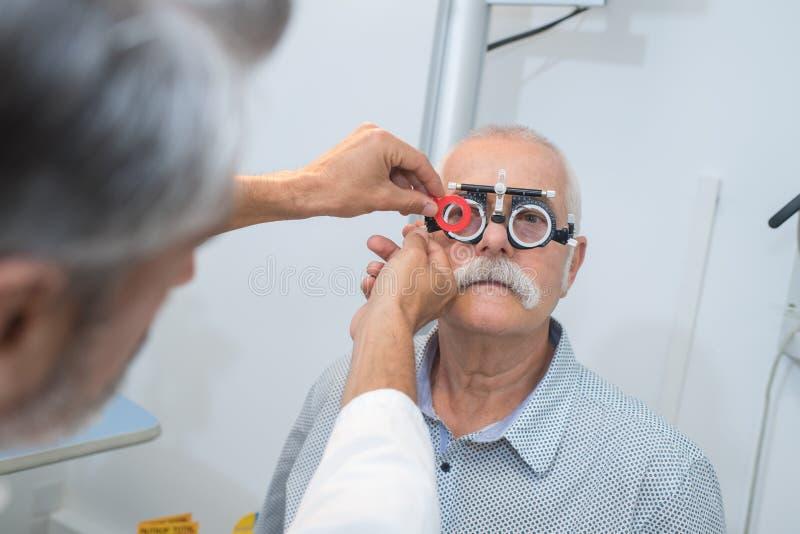 Homme supérieur en gros plan vérifiant la vue dans la clinique photographie stock