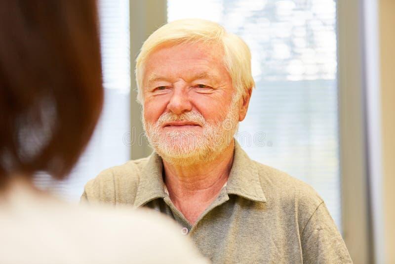 Homme supérieur en tant que patient parlant à un docteur féminin photos stock