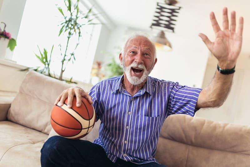 Homme supérieur encourageant pour un match de basket photographie stock