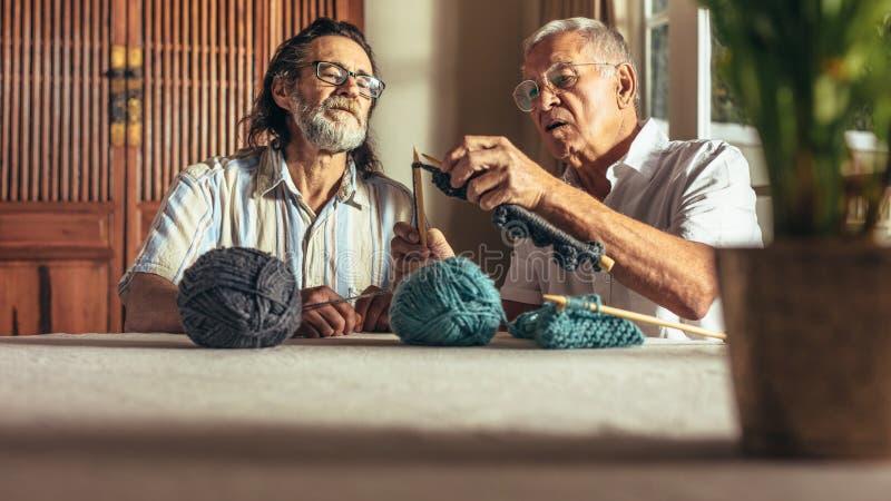 Homme supérieur enseignant à ses amis l'art du tricotage photos stock
