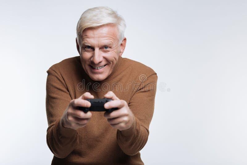 Homme supérieur enthousiaste jouant le jeu vidéo images stock