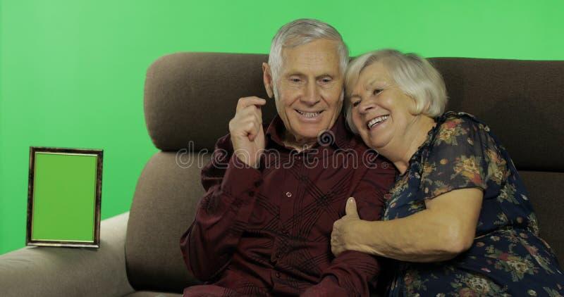 Homme supérieur et femme âgés s'asseyant ensemble sur un sofa Femme avec son mari photos libres de droits