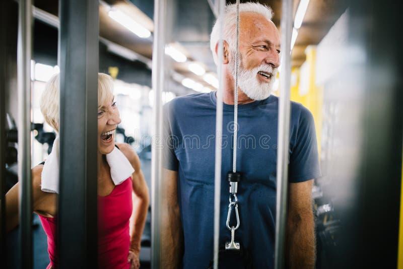 Homme supérieur et femme convenables faisant des exercices dans le gymnase pour rester sain photographie stock libre de droits