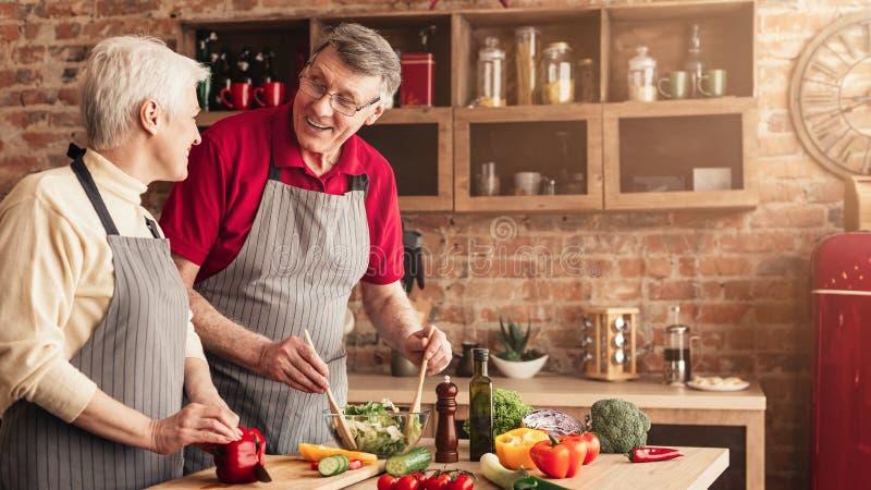 Homme supérieur et femme faisant cuire le déjeuner sain ensemble dans la cuisine images libres de droits
