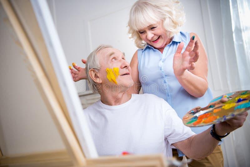 Homme supérieur et femme heureux dans l'atelier d'art photo stock