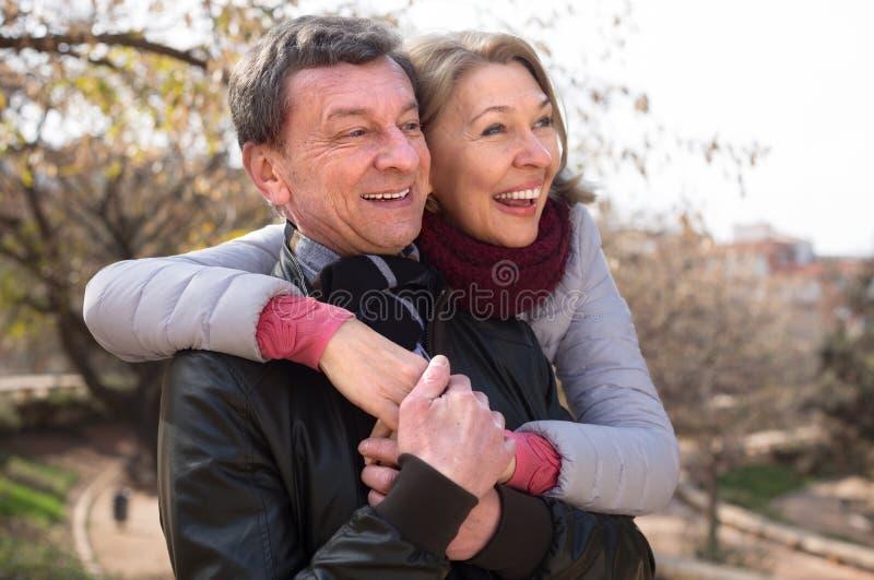 Homme supérieur et femme mûre ensemble contre les arbres blured du parc photographie stock libre de droits