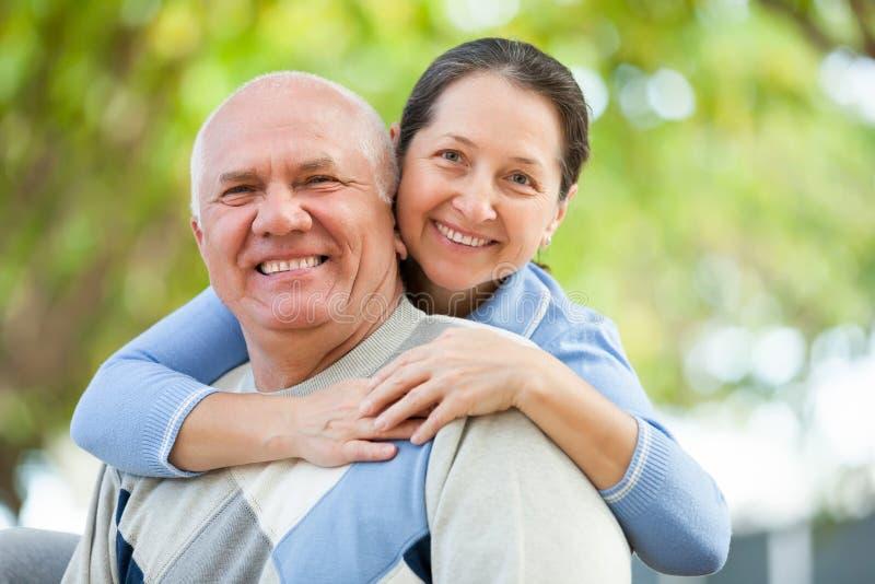 Homme supérieur et femme mûre contre les arbres blured images libres de droits
