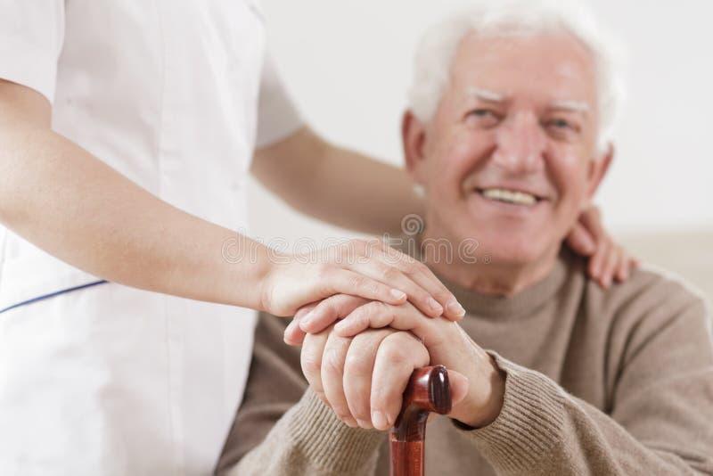Homme supérieur et infirmière utile photographie stock