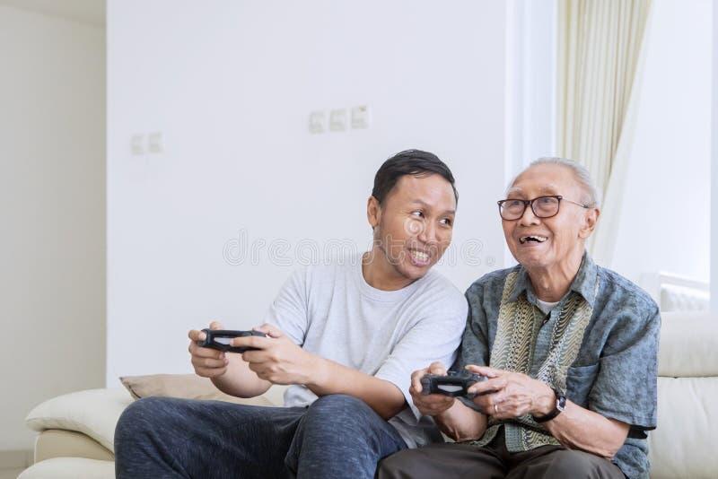 Homme supérieur et son fils jouant des jeux vidéo image libre de droits