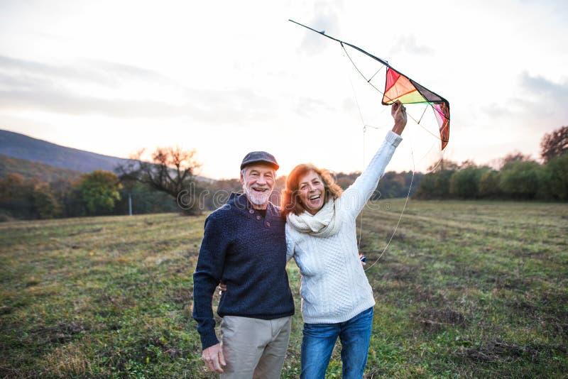 Homme supérieur et une femme avec un cerf-volant dans une nature d'automne au crépuscule photos libres de droits